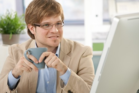 Young businessman sitting at office desk, holding coffee cup, looking at screen. Stock Photo - 7129933