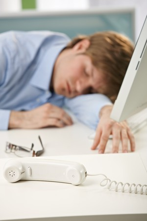 beiseite: M�de B�roangestellter schlafen am Schreibtisch, selektiven Fokus auf Telefon beiseite.
