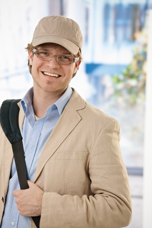 Casual young businessman wearing baseball cap leaving office, smiling.