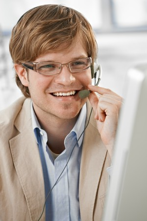 Closeup portrait of happy young businessman talking on headset, smiling. Stock Photo - 7130131