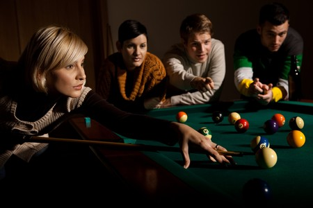 concentrating: Woman concentrating on snooker game, leaning on table, aiming at ball, holding cue, friends watching in background.