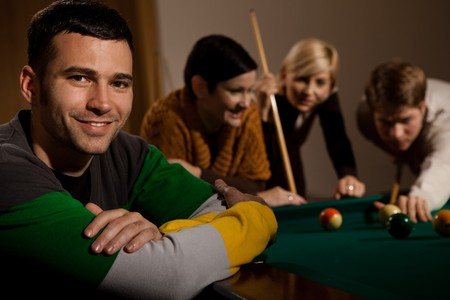 Portrait of smiling young man at snooker table, friends playing in background. photo