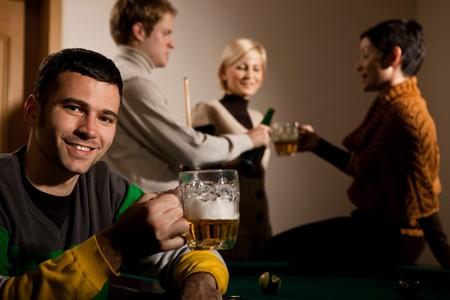 man drinkt bier: Portret van een jonge man bier drinken op snookertafel glimlachen, vrienden hebben drinken in de achtergrond. Stockfoto