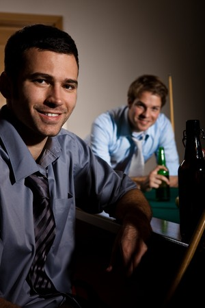 Portrait of two men at snooker table, having beer, smiling. photo