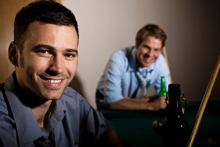 Portrait of young happy man at snooker table, holding cue, having beer, friend smiling in background. photo