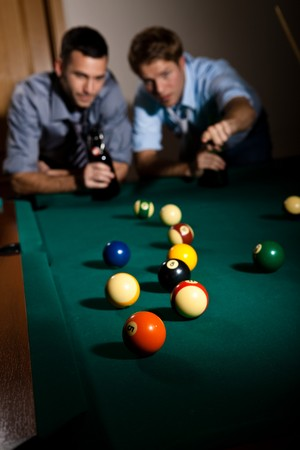 Two young men discussing snooker game at table, having beer, focus on snooker balls. photo