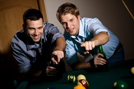 billiard: Two young men discussing snooker game, having beer, pointing at table.