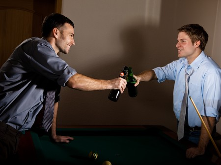 Young men clinking beer bottles at snooker, smiling at each other, celebrating game. photo