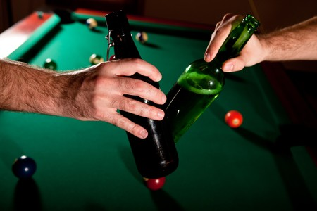 colored bottle: Men clinking beer bottles above snooker table.