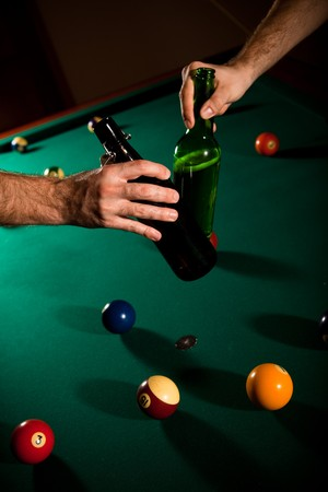 vertical bars: Men clinking beer bottles above snooker table full of balls.