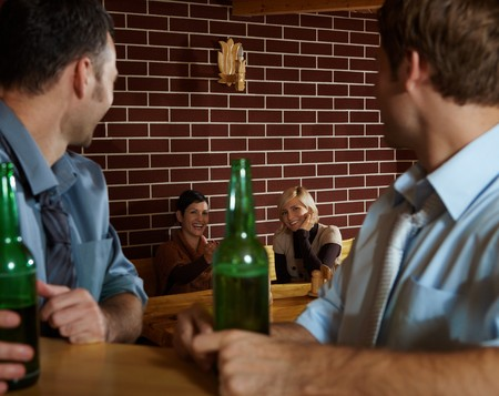 Young people sitting in bar, young men looking at smiling women sitting at table. photo