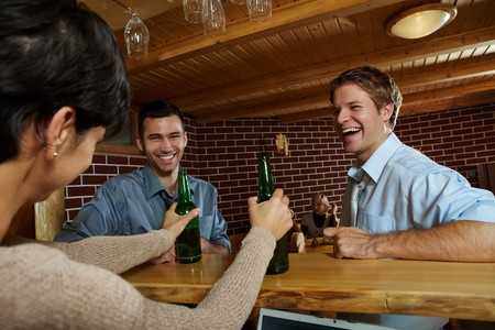 Young men laughing at woman drinking beer in pub.