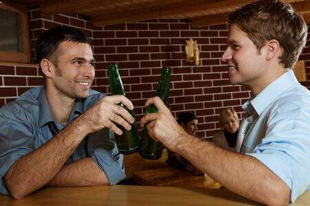 Two men drinking beer in bar, clinking bottles, smiling, women talking in background. photo