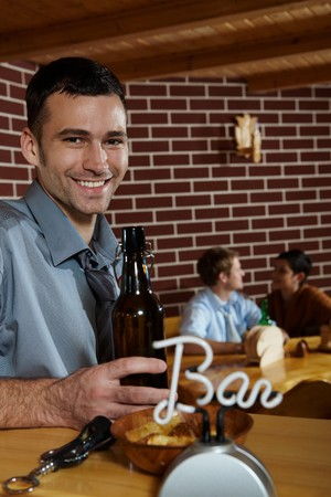 Portrait of young man standing at bar in pub, drinking beer, smiling at camera. photo