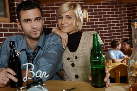 Portrait of young couple in bar, standing at counter, looking at camera. photo