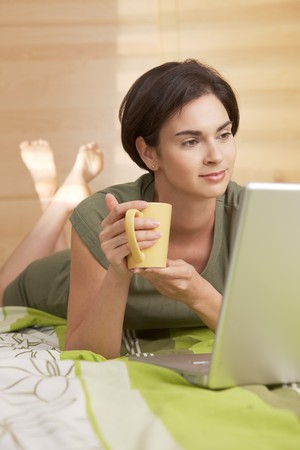 nightdress: Mid-adult woman having morning coffee in bed, looking at computer. Stock Photo