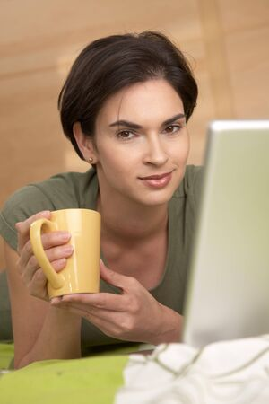 nighty: Portrait of smiling woman having morning coffee in bed, looking at camera.