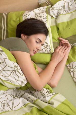 Mid-adult woman smiling in sleep in colorful bedclothes. photo