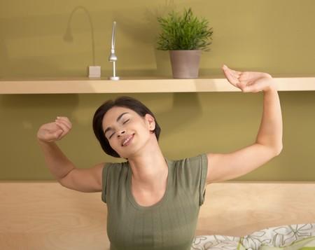 levantandose: Mujer feliz despertarse de estiramiento y sonriente en la ma�ana con los ojos cerrados.