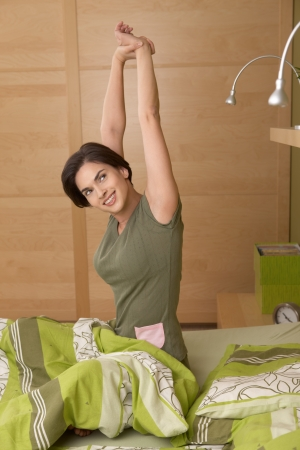 up wake: Smiling woman waking up, stretching, sitting in bed in morning.