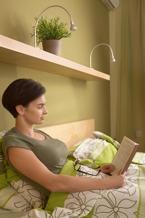 Mid-adult woman reading book in bed, alone in bedroom. photo