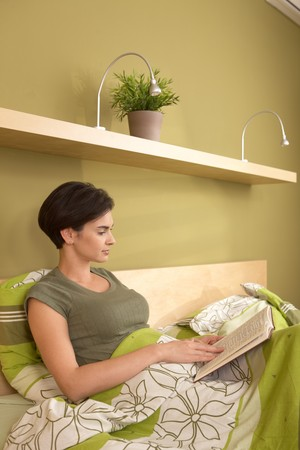 Mid-adult pretty woman reading book, sitting in bed in bedroom. photo