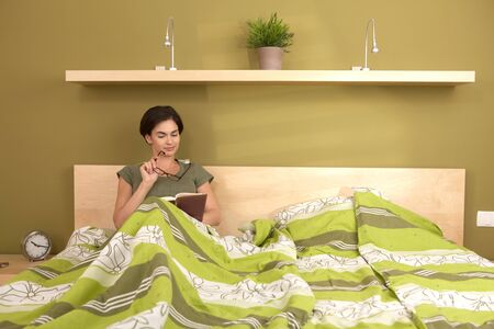 Woman reading book, holding glasses, sitting alone in double bed. photo