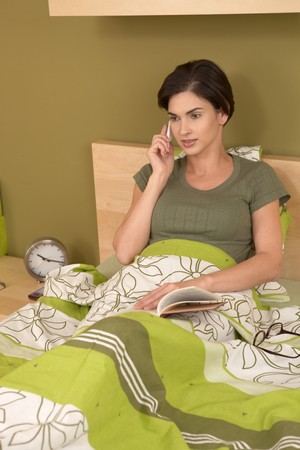 Woman talking on mobile phone, sitting in bed, holding book in bedroom. Stock Photo - 7130338