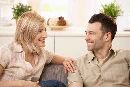 Smiling young couple sitting at home on sofa. Stock Photo - 7217378