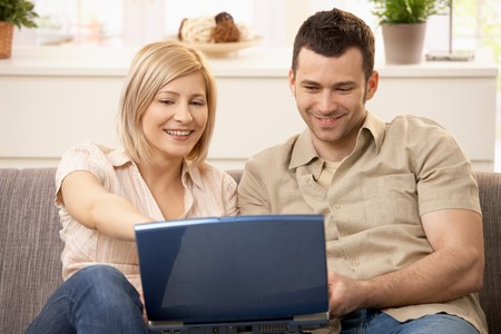 Smiling couple sitting together browsing internet on laptop computer.