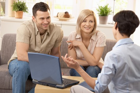 three color: Advisor and smiling couple in discussion in bright living room. Stock Photo