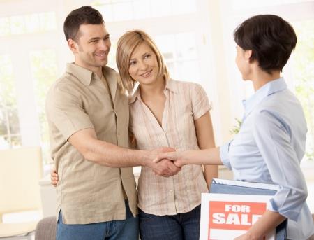buen trato: Agente inmobiliario felicitar a la joven pareja en la decisiones acuerdo sobre la nueva casa.