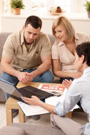 Jong koppel luisteren naar vastgoed makelaar weer gegeven: nieuwe huis op laptop.