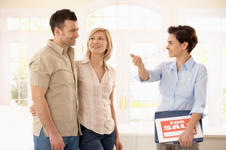 30s: Happy couple checking new house with estate agent. Stock Photo