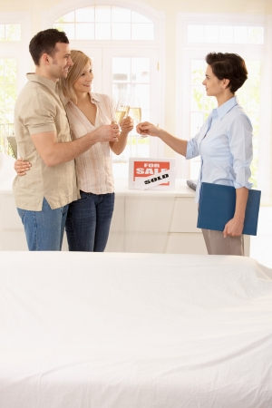 Estate agent and couple celebrating deal of buying new house. Stock Photo - 7217271