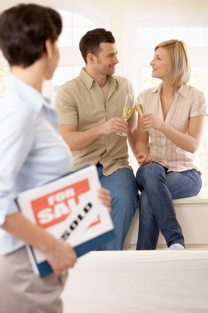 Estate agent holding for sale sign looking at celebrating couple holding champagne glasses in focus. photo