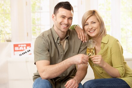 Portrait of happy couple celebrating purchase of new home, laughing at camera. photo