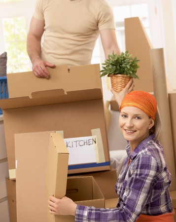 Couple packing boxes to move to new house. photo