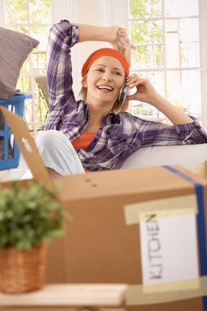 moving house: Laughing woman taking break at moving house, talking on mobilephone. Stock Photo