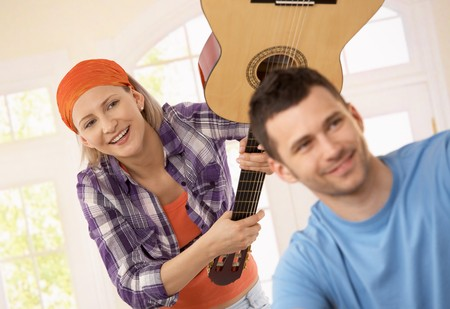 Laughing woman playing joke pretending to hit smiling man on head with guitar. photo