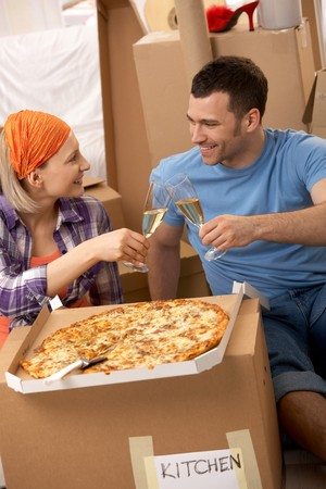 Happy couple having pizza and clinking champagne glasses at lunch break of moving house. photo