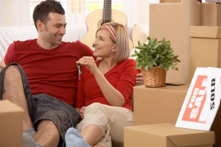 Happy couple sitting in middle of boxes smiling, holding keys of new house. photo