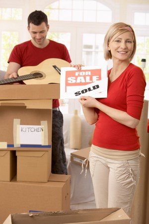 Happy woman holding sold sign in new house, smiling man unpacking boxes in background. photo