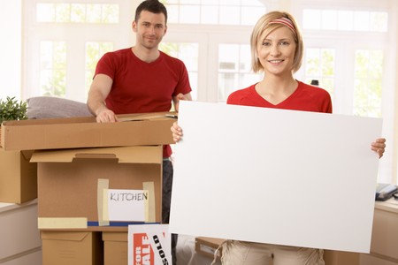 Smiling couple unpacking in new place, copyspace in blank poster. photo