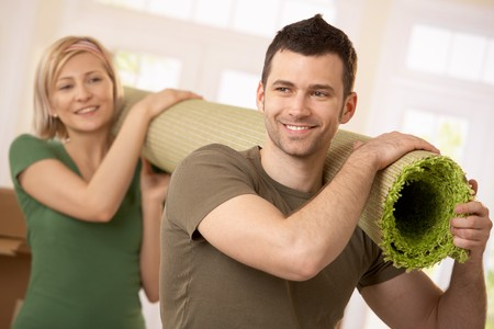 Happy couple carrying carpet together at moving house. photo