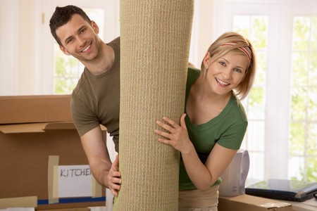 Portrait of couple moving house, holding carpet rolled up, smiling. photo
