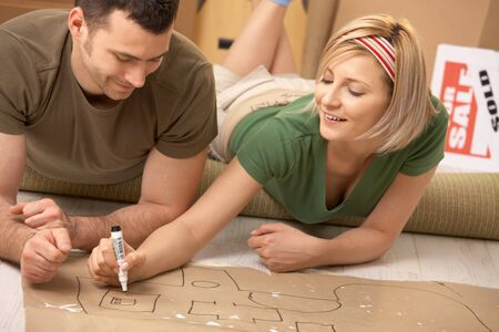 Happy couple planning to furniture the new house after moving in, girl drawing with marker on paper. photo