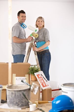 Portrait of young couple painting their new home, smiling, standing together on ladder. photo