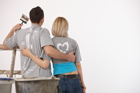 after work: Couple standing together, embracing, holding paint brush, looking at white wall after painting.