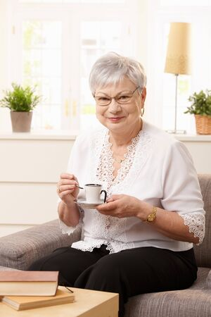 Portrait of senior woman sitting on sofa drinking coffee at home, looking at camera smiling. Stock Photo - 7217337